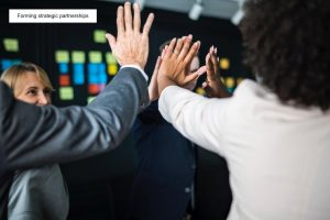 People high fiving - illustrating an article on Forming strategic partnerships