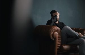 Man sat on sofa, holding his head to illustrate blog are you disempowering your team
